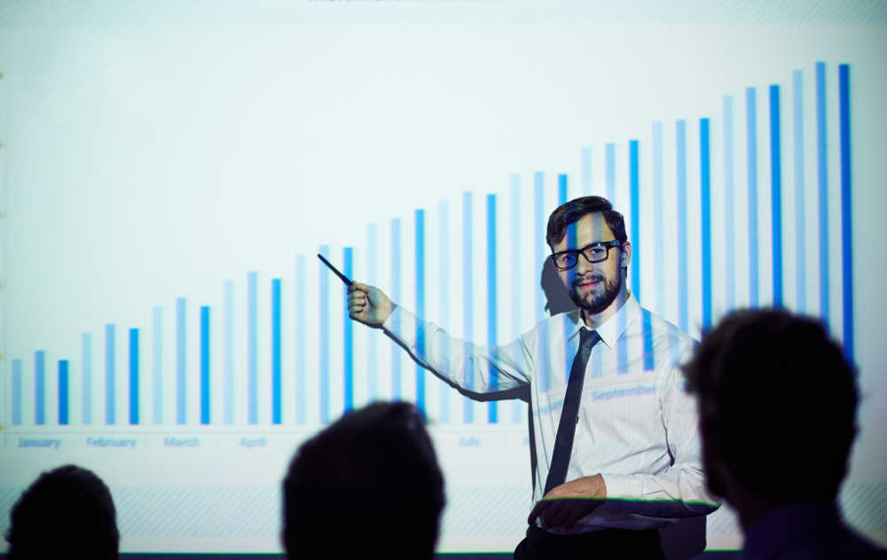 Businessman presenting report of progress on the wall